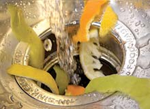 Photograph of kitchen scraps being washed into an in-sink garbage disposal