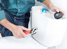 Photograph of plumbers installing parts in a toilet tank repair